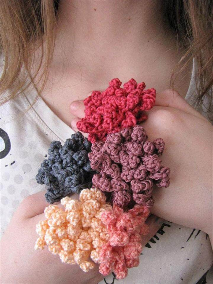 Crochet flowers bound by branches.
